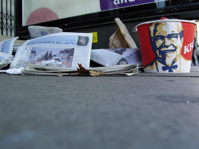 What do I need to balance the piles of discarded 'free' papers? Oh yeah, a KFC bucket!